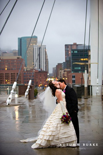 downtown denver wedding urban cityscape bride and groom in rain union station millenium bridge